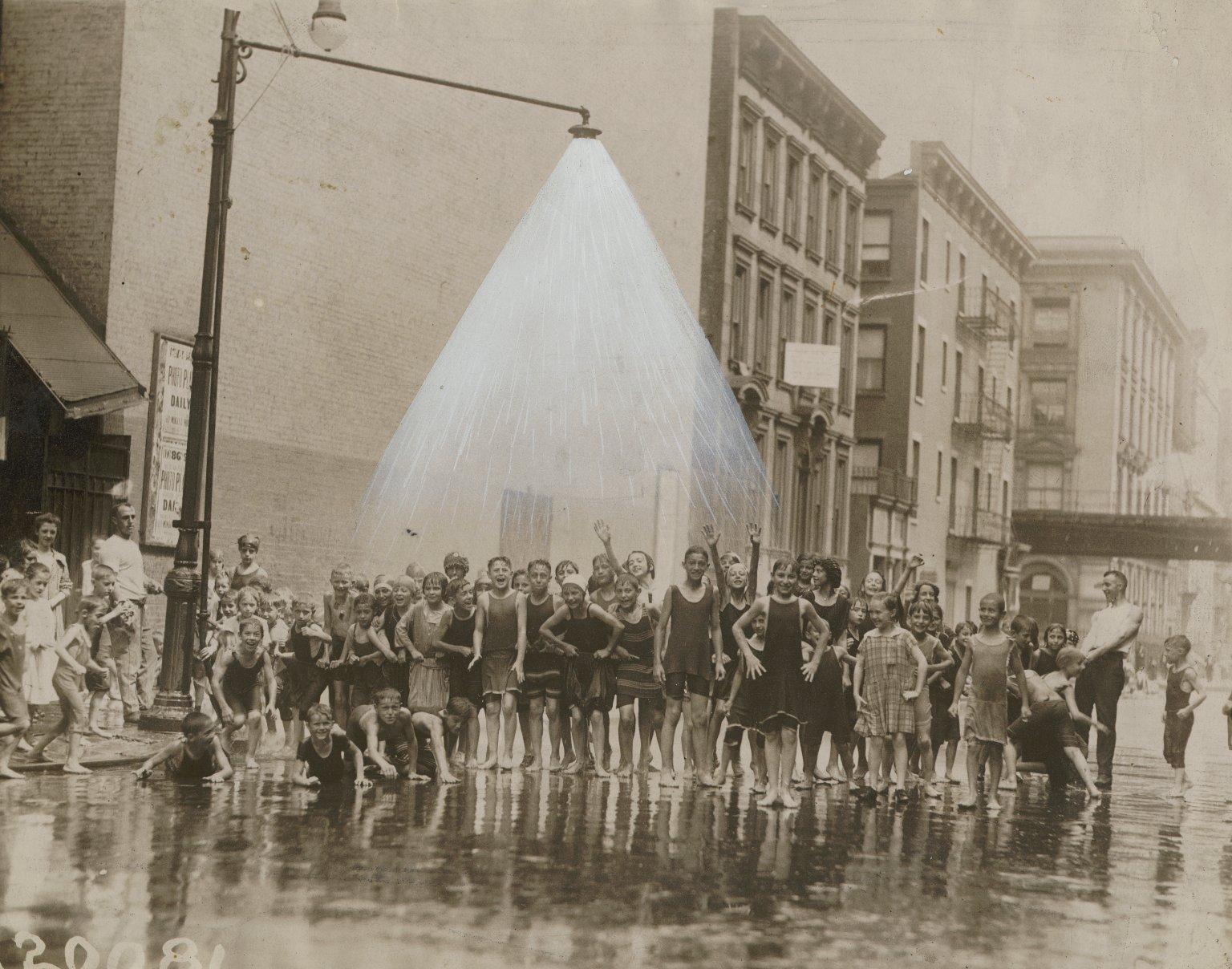 Пожарные установили спринклер для развлечения детей на перекрестке 85-ой улицы и Лексингтон Авеню, Нью-Йорк, США. Август 1920 года