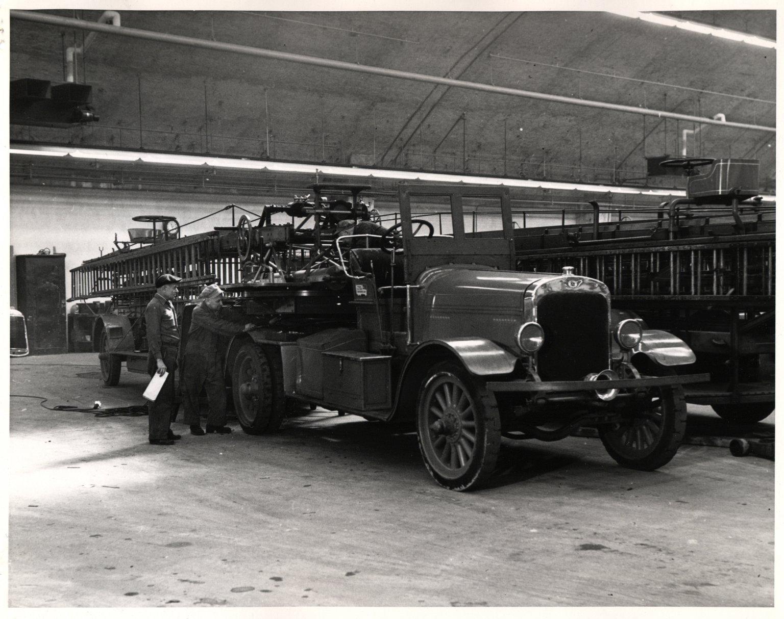 Механики осматривают автолестницу в мастерских. Нью-Йорк, США. 1930-е