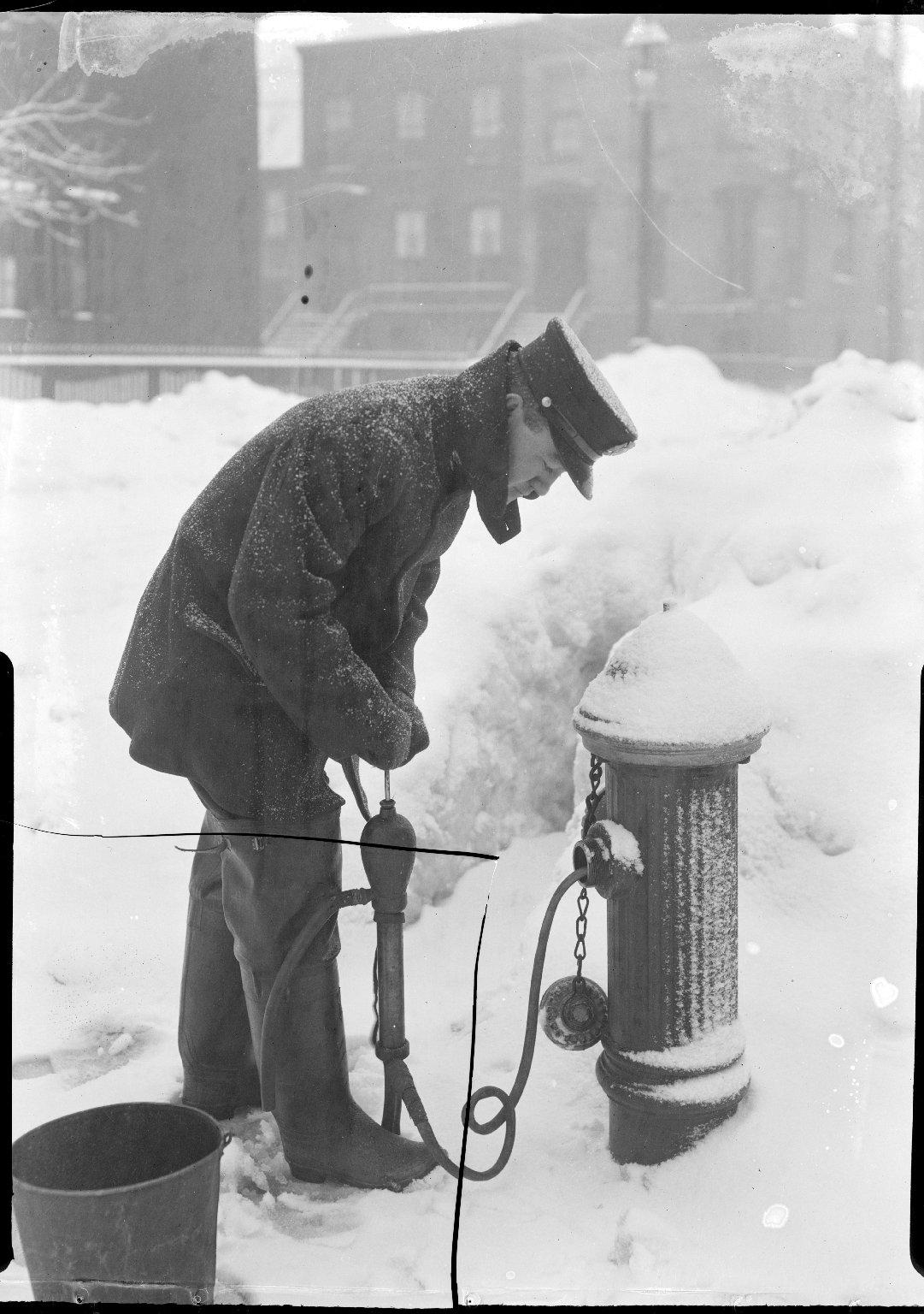 Пожарный качает воду из замерзшего пожарного гидранта. Нью-Йорк, США. 1901 год