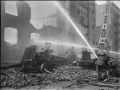 Уничтоженный пожаром рукавный автомобиль. Двое пожарных проливают  здание. Нью-Йорк, США. Начало 20 века