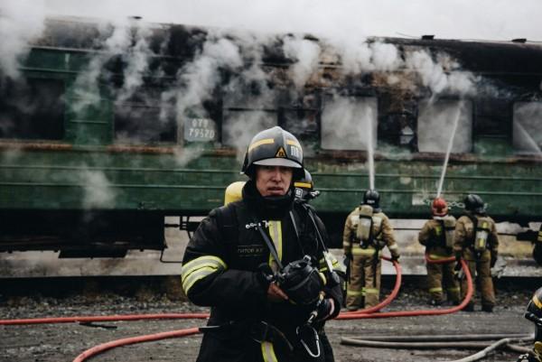 Пожарный во время учений по тушению поезда