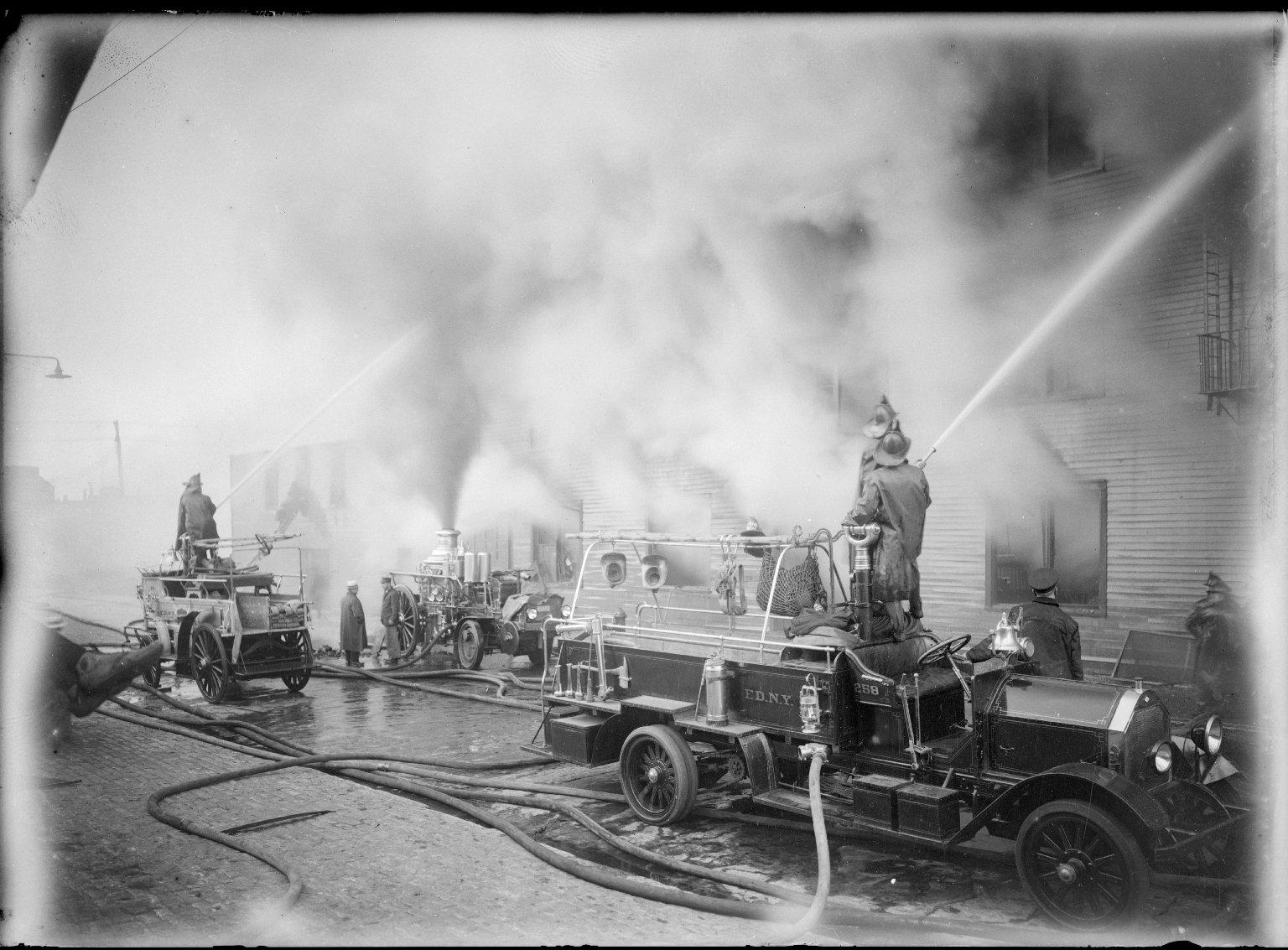 Тушение пожара. В центре паровой пожарный насос, перевозимый трактором Christie. Пожарная линейка Seagrave слева. Справа пожарный автомобиль с лафетным стволом Seagrave. Нью-Йорк, США. 1915 год.