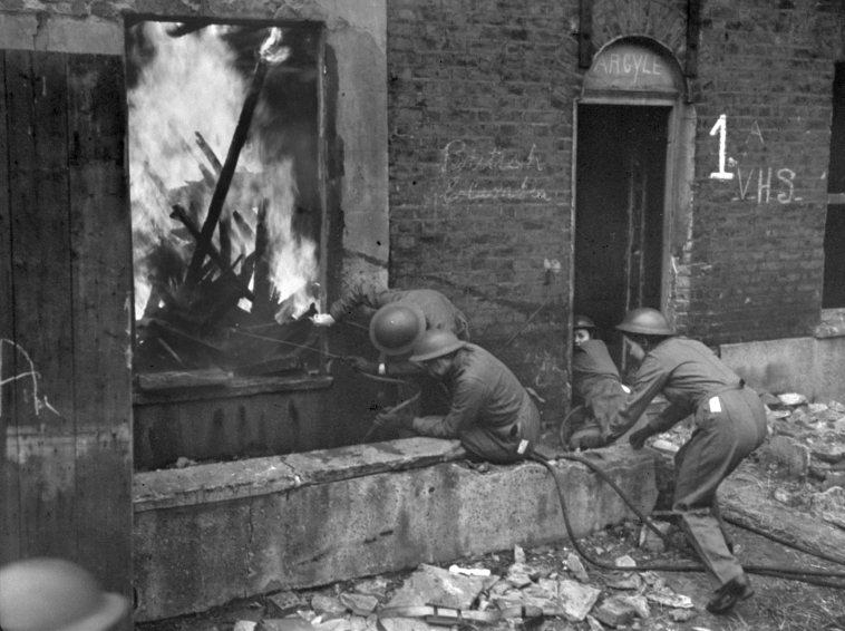 Военнослужащие Канадского Женского Армейского корпуса (C.W.A.C.) принимают участие в учениях по тушению пожаров. Лондон, 28 февраля 1943 года