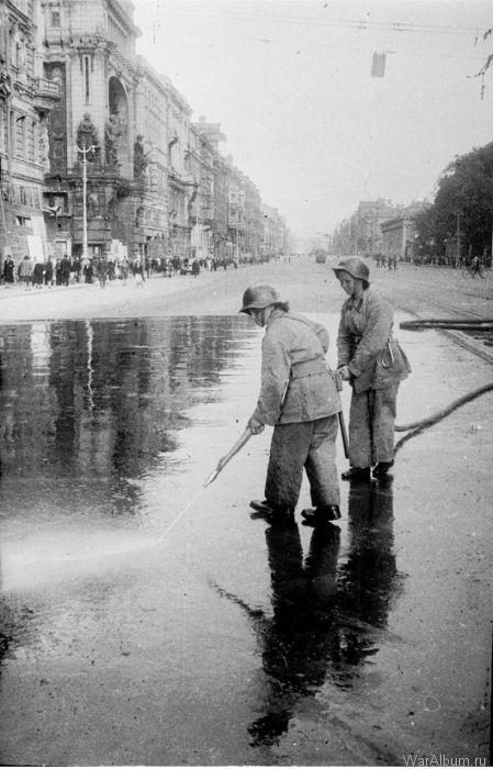 Пожарные смывают с асфальта на Невском проспекте кровь ленинградцев, убитых в результате немецкого артобстрела, 1943 год