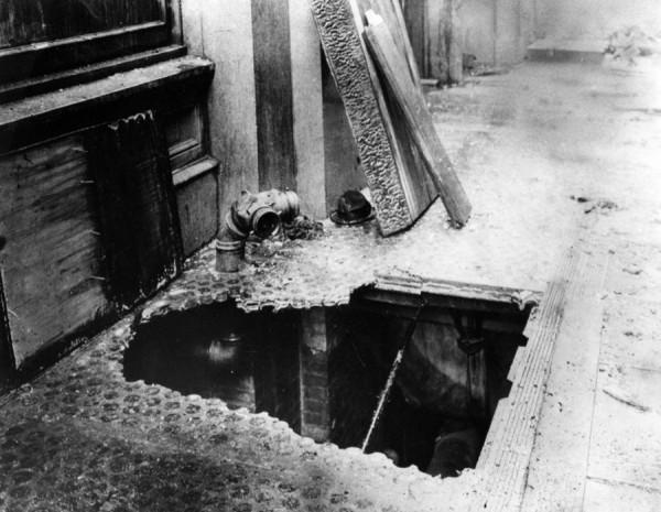 Стеклянная световой люк подвала под тротуаром был пробит упавшим телом жертвы, прыгнувшей из окна, чтобы избежать смерти в огне.